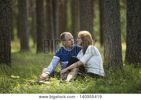 Young couple sitting in the grass near the tree in the Park . Honeymoon.