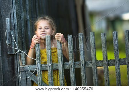 Cute little girl peeking out from behind the fence in the village.