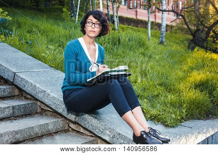 Student girl holding notebook and books. Young beautiful woman sitting on stairs and writing notes.