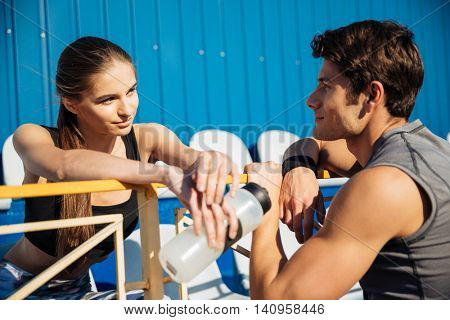 Close up portrait of a young couple talking on athletics track field at the stadium