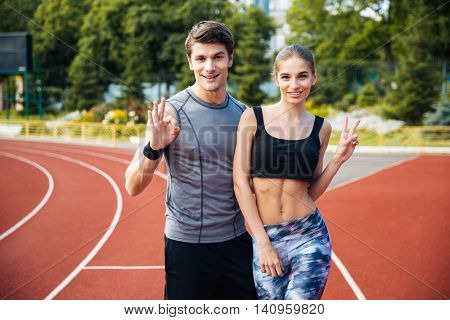 Full length shot of young man and woman standing on athletics race track at the stadium showing v sign and okay sign
