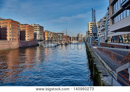 Old brick and modern buildings along a waterway of the famous Speicherstad Hamburg