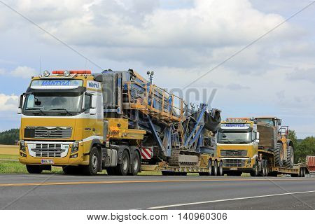 SALO, FINLAND - JULY 30, 2016: Two Yellow Volvo FH16 semi trucks of Mantyla E & E in heavy equipment haul stop for a moment by road in South of Finland. The trucks transport screener and Cat wheel loader on drop deck trailer.