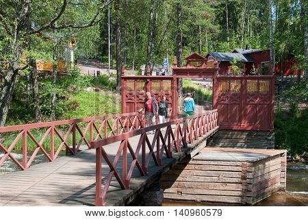 KOTKA, FINLAND - JUNE 26, 2016: People on the bridge in territory of The Russian Emperor Alexander III fishing lodge near Langinkoski Rapid on Kymi River. National Urban Park.