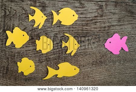 Group of fish with one pointed against the flow on wooden background