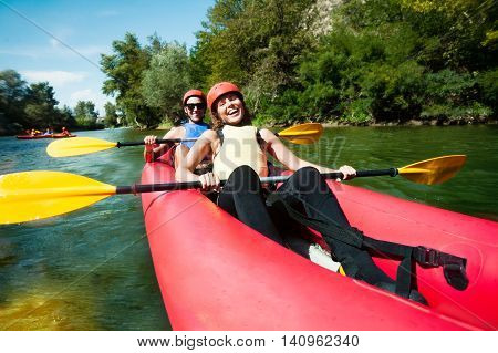 A female and  a male in red inflatable canoe having fun in calm waters of a river.