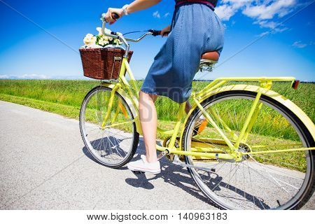 Woman Riding Vintage Bicycle With Wicker Basket In Countryside