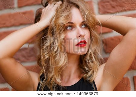 Beautiful blonde woman with natural make-up and gray eyes on brick background. Shoot on fast aperture