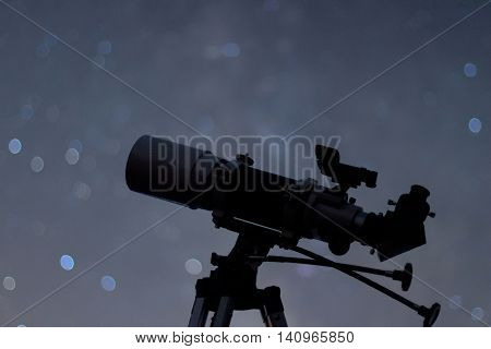 Silhouette of Telescope in real night sky. Blurred night sky. Blurred milky way. Refractor type telescope