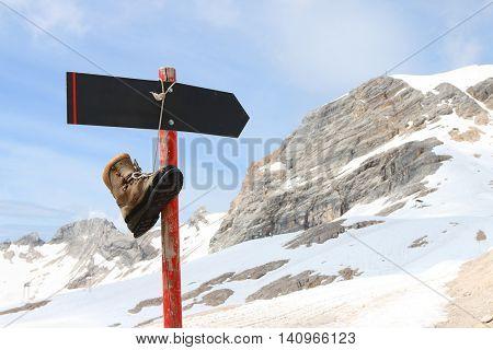 Old hiking boot on empty signpost in snowy alpine landscape near Garmisch Partenkirchen in Germany. Skiing resort under Zugspitze.