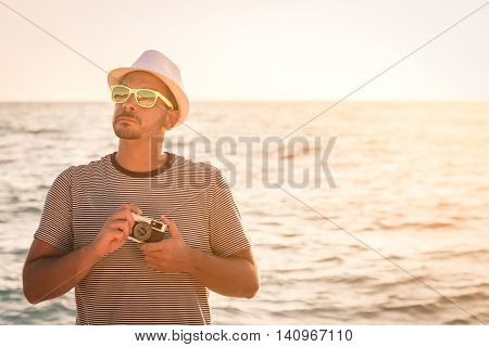 Portrait of young tourist guy holding retro camera at the seaside ready to take photos. Summer vacation and travel concepts. Copy space.