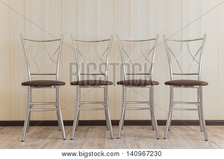 Four metal chair in a row against the wall
