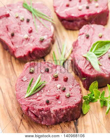 Pieces of beef tenderloin on the wooden cutting board.