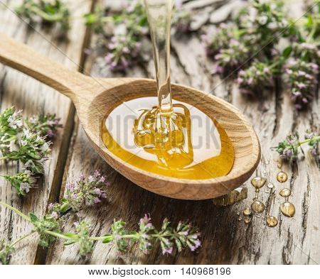 Herbal honey pouring into the wooden spoon. Spoon is on old wooden table surrounded with levender flowers. Honey drops.