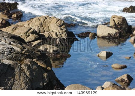 This is an image of a quiet tide pool in the Point Lobos State Preserve taken on a clear sunny day.