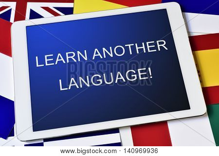 the text learn another language in the screen of a tablet computer surrounded by flags of different countries
