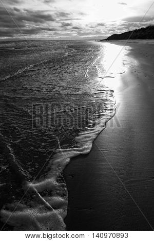 The tide slips in over the silky sand at Druridge Bay as the Winter sunlight glints on the shoreline