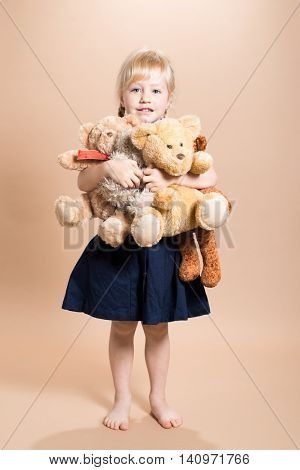 Little girl with her arm full of teddy bears