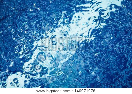 transparent water surface in swimming pool with bubbles and ripples