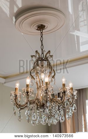 Beautiful crystal chandelier in ambient light in luxury home