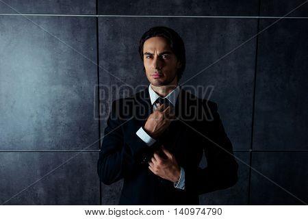 Portrait Of Confident Harsh  Man  Correcting His Black  Tie