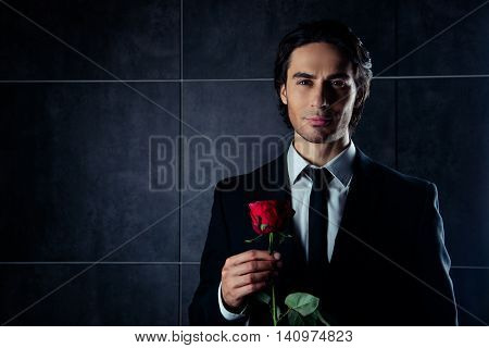 Portrait Of Handsome Romantic Young Man In Formalwear  Holding Red Rose