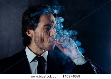 Portrait Of Brutal Handsome Man With Stubble Smoking A Cigar