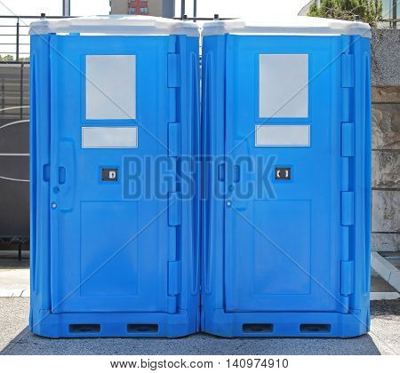 Two Blue Plastic Mobile Toilet Cabins Outside
