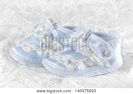 Blue baby booties on a lace background