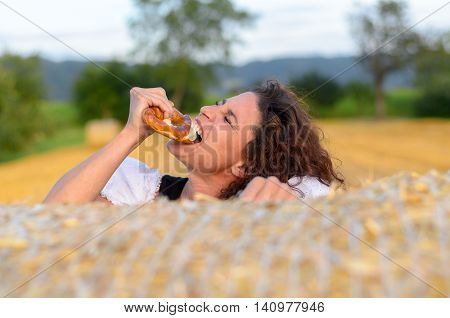 Young Woman Biting Into A Brittle Pretzel