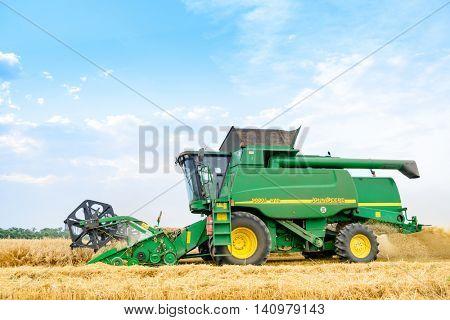 ZAPORIZHZHYA, UKRAINE - July 28, 2015: John Deere Combine Harvester Harvesting Wheat in the Field.