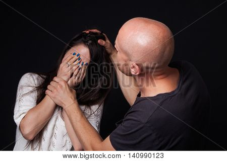 Domestic violence - man beating the woman she is closing her face with hands black background