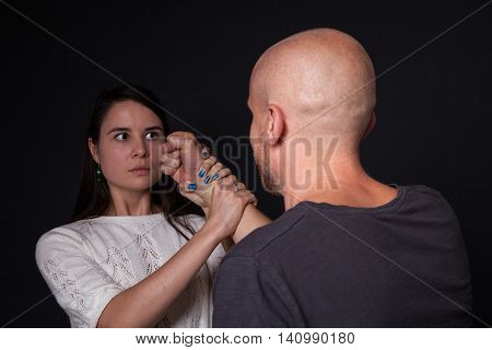 Domestic violence - husband trying to beat wife she is getting hold of his fist dark background