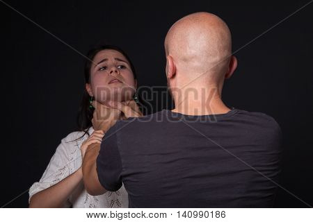 Domestic violence - man is choking woman black background