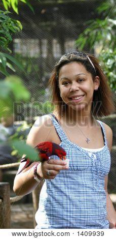 Biracial Young Woman Feeding A Bird