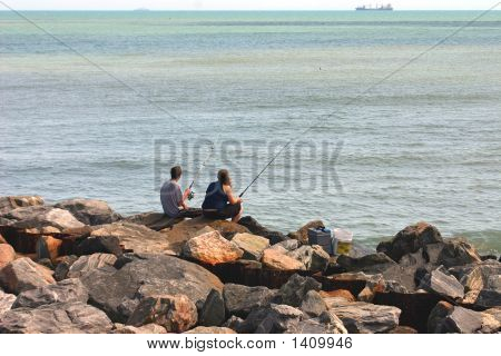 Couple Fishing On Rocks