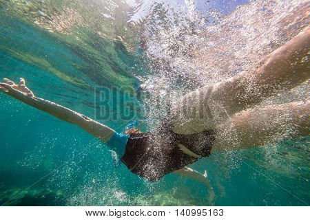 Close up of young female free diving in tropical blue sea surrounded by water bubbles.