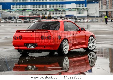 driver drives a Nissan skyline R 32 red, on a wet road 9 July 2016 in Khabarovsk, Russia