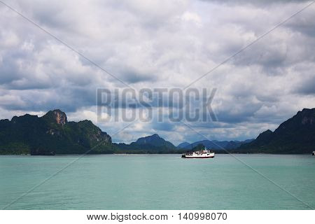 Sea, mountain and a ferry with cloudy sky