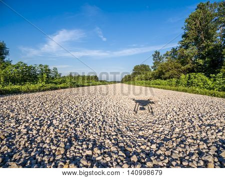 shadow of a quadcopter  drone flying low  with a camera over gravel road