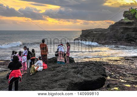 Bali,Indonesia-May 28,2010:Group of tourist enjoying sunset view at Tanah lot,Bali,Indonesia.It is a rock formation off the Indonesian island of Bali & home to the pilgrimage temple Pura Tanah Lot.