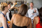 Female friends ordering drinks from barkeeper in restaurant poster