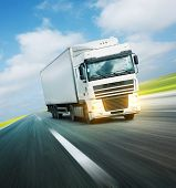 pic of delivery-truck  - White truck on asphalt road under blue sky with clouds - JPG