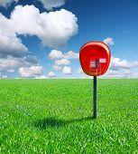 Постер, плакат: Красный общественного телефона устройство на зеленом поле с синим небом