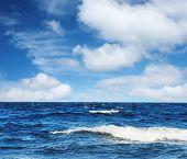 Постер, плакат: Синее море с волнами и пушистые облака на голубое небо