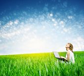 Young woman with laptop sitting on green grass and looking to a sky