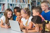 School kids using laptop in library at school poster