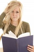 stock photo of frazzled  - A woman is looking a little frustrated and holding a book - JPG