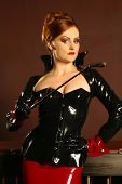 image of domme  - Powerful dominatrix type redhead woman wearing a latex jacket and skirt holding a riding crop in a strong stance - JPG