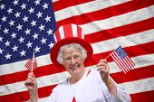 foto of waving american flag  - Patriotic senior woman waving flags and smiling - JPG
